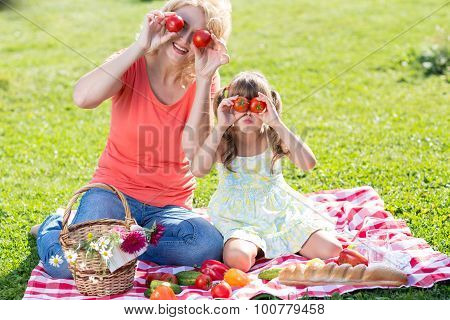 Child and mother sitting outdoors and picnicking together