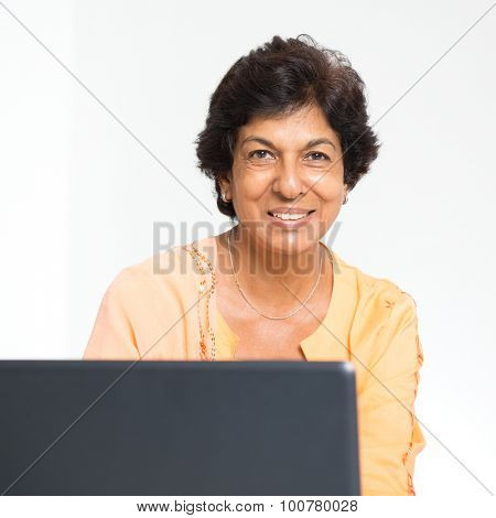 Elder people and modern technology concept. Portrait of a 50s Indian mature woman using internet at home. Indoor senior people living lifestyle.