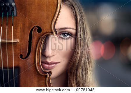 Pretty Young Woman Peeking Behind Violin