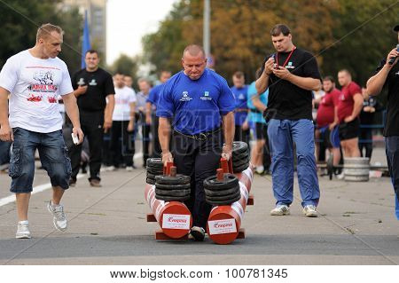 Orel, Russia, September 5, 2015: Strong Male Powerlifter Carries Two Heavy Dumbbells In Competition