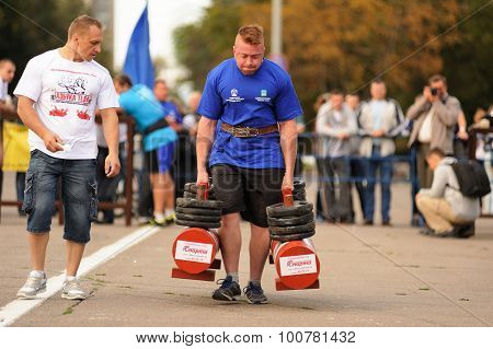 Orel, Russia, September 5, 2015: Man Powerlifter Carries Two Heavy Dumbbells In Competition