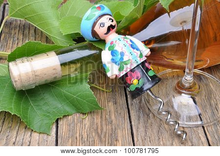 Hungarian decorative corkscrew, wine bottle and glass of wine on the wooden table