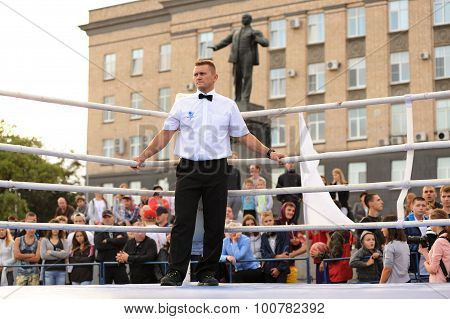 Orel, Russia, September 5, 2015: Box Referee Standing In Empty Ring With Lenin Monument On The Backg