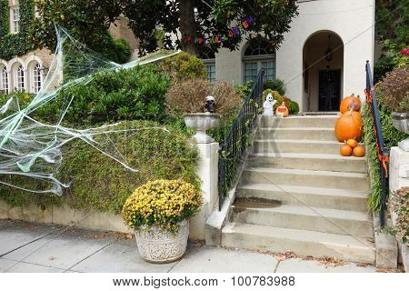 Pumpkins and scary decorations on front steps of home during Halloween / Thanksgiving season