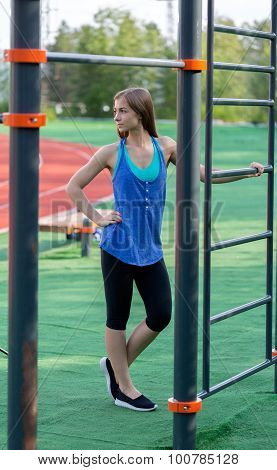 Beautiful Girl In Sportswear On The Playground In The Park.