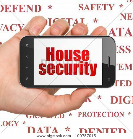 Privacy concept: Hand Holding Smartphone with House Security on display