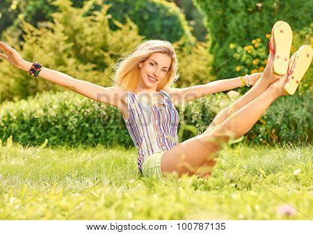 Beauty playful woman relax in summer garden lying on grass