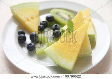 Yellow Melon Wedges With Kiwifruit And Berries