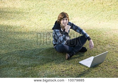 Teenage Boy Using Laptop Outdoors On Grass