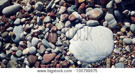 Big Round White Stone Amongst Grey And Brown Pebbles On The Beach.