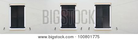 Black french shutters with stucco wall