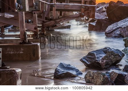 Tidewater Flowing between Wooden Pier and Rocks