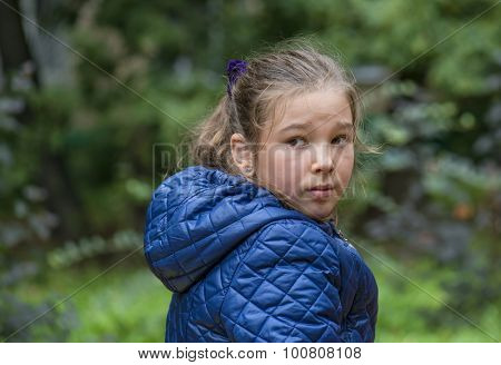 Outdoor portrait of a little girl in autumn jacket