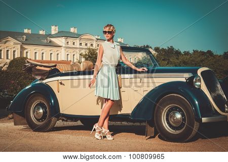 Beautiful lady near classic convertible