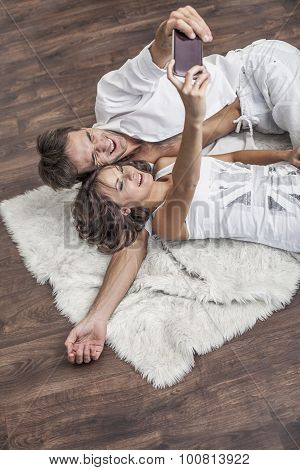 Couple Man And Woman Taking Selfies On The Floor On The Carpet