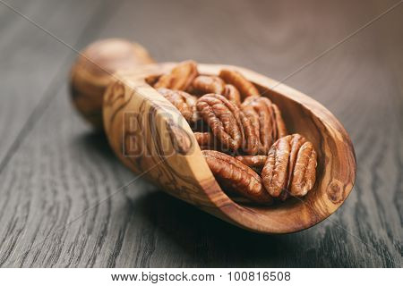 pecan nuts in olive wood scoop on oak table
