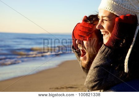 Couple In Love Playing At Sunset In Winter On The Beach