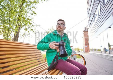 people, photography, technology, leisure and lifestyle - happy young hipster man holding digital camera with big lens and looking for subject on city street