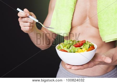 Closeup of a fit man holding a bowl of fresh salad on dark background