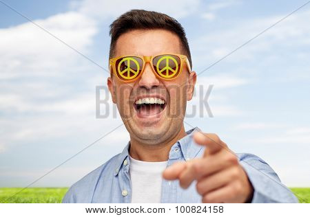 summer, ecology, emotions and people concept - face of laughing middle aged man in sunglasses with green peace symbol pointing finger on you over blue sky and grass background