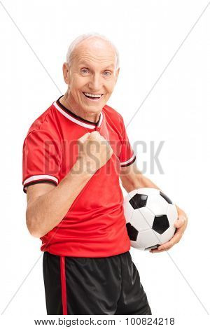 Vertical studio shot of a joyful senior man with gripped fist holding a football and looking at the camera isolated on white background
