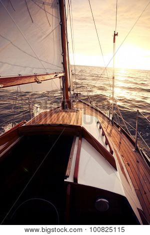 Classic sailing yacht sails towards the setting sun