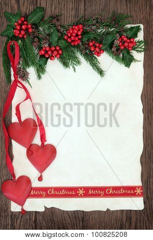 Christmas background border with merry christmas ribbon and red heart bauble decorations, holly and winter greenery on parchment paper over old oak wood.