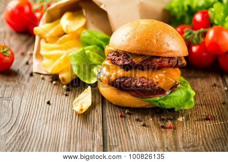 Hamburger Vintage style. Burger with two fried beef cutlets and fresh tomatoes with lettuce on wooden table. Cheeseburger served with French Fries in crumpled brown paper. Junk food concept