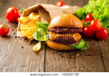 Juicy and fragrant hamburger with fried potatoes on rustic wooden surface. Cheeseburger with tasty buns and juicy meet cutlet with fresh vegetables served with French Fries on a dark wooden table.