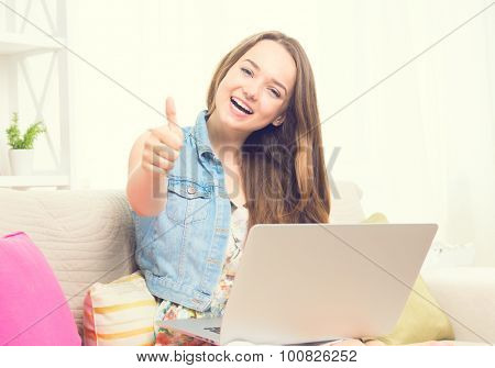Pretty teenage girl sitting on sofa at home with her laptop, making thumb up gesture. Beauty girl with laptop computer Vintage style. Smiling and laughing