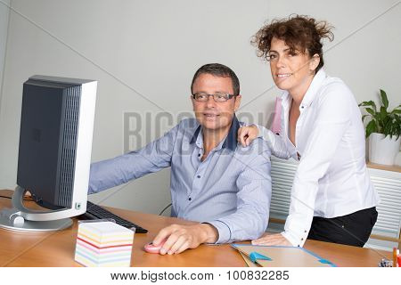 Two Bookshop Managers Working On Laptop.