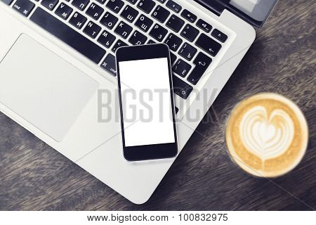 Blank Smartphone On Laptop With Cup Of Coffee On A Wooden Table, Mock Up