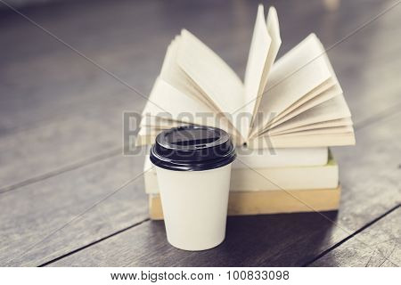 Coffee To Go And Pack Of Books On A Wooden Table