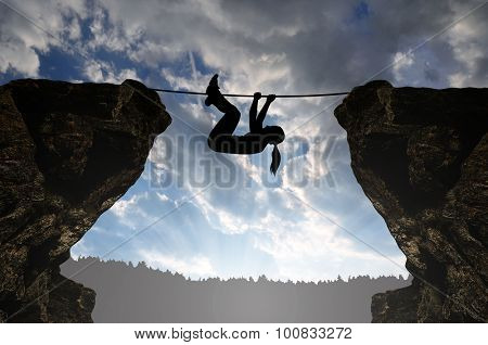 Silhouette girl climbs on a rope over an abyss.