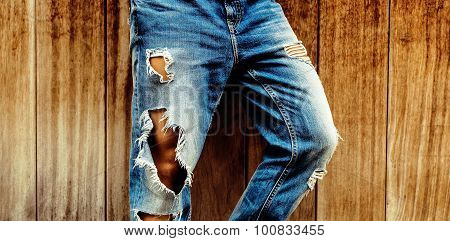 Stylish Torn Blue Jeans On Wooden Background. Unisex Style