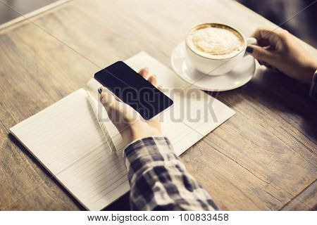 Girl  Hand With Smartphone, Blank Diary And Cup Of Coffee On A Wooden Table