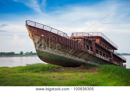 Old rusty abandoned ship near the river