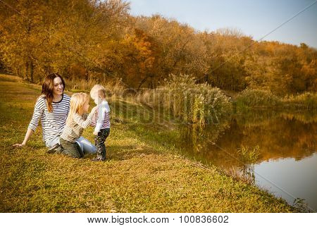 Portrait Of Smiling Mother And Daughters On Autumn Lake