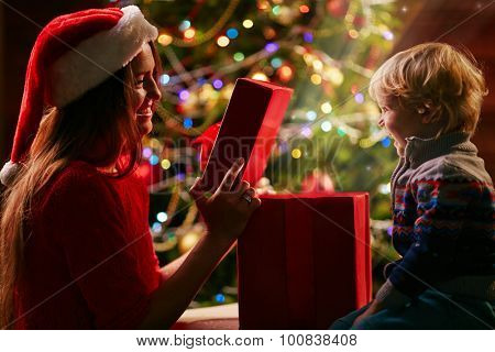 Joyful boy looking at his mother while she holding cover from open giftbox