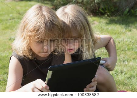 Two Boys Are Looking To The Tablet Outdoors