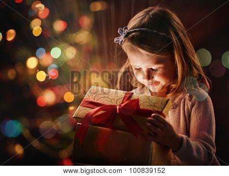 Pretty girl opening magic giftbox on Christmas day