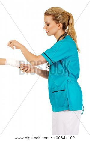 Young female doctor bandaging woman hand.