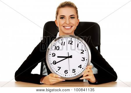 Happy businesswoman with clock behind the desk.