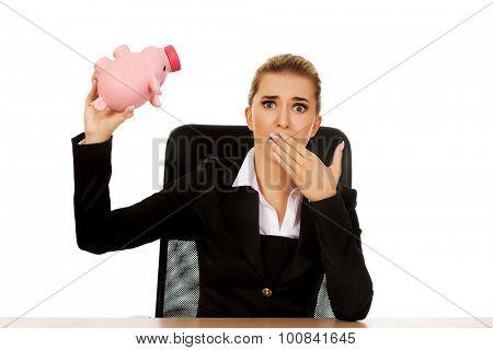 Worried businesswoman with a piggybank behind the desk.