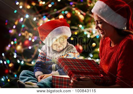 Cute boy in Santa cap looking at light in giftbox being opened by his mother