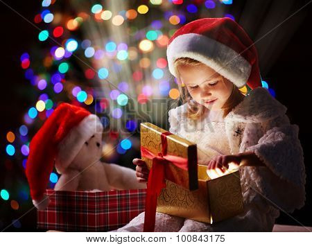 Curious girl putting her hand into open giftbox to touch unusual Christmas present
