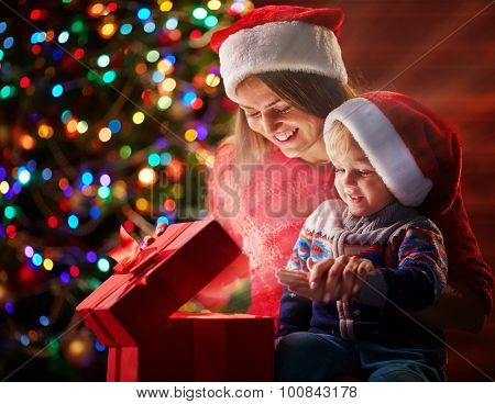 Happy woman and her son in Santa caps looking at light from red giftbox