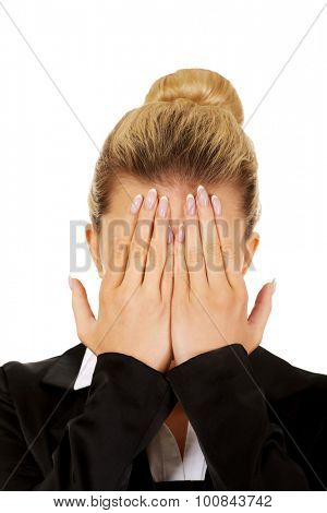 Troubled business woman covering her face with hands.