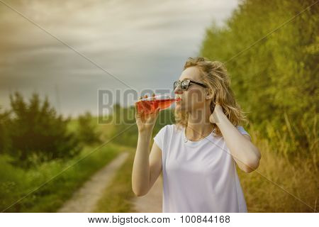 Young beautifil woman drinking red softdrink.