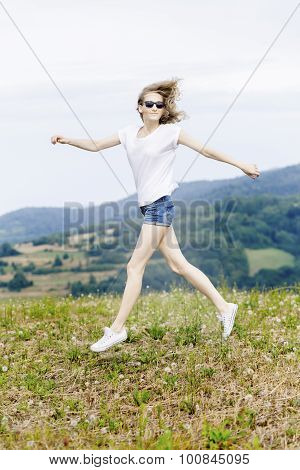 Happy woman jumping on meadow.